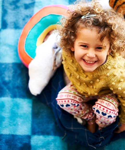 A small child smiling and sitting on a dark blue throw on a checkered blue rug.