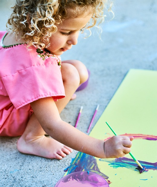 A small child painting bright colours on yellow paper, on a concrete floor.