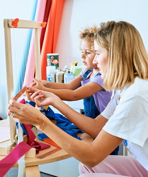 Chloé and her daughter weaving strips of fabric on a wooden loom.