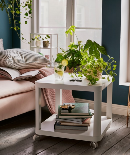 Cube-shaped, two-level, wheeled side table – books below, plants and a glass on top – next to a chaise longue.