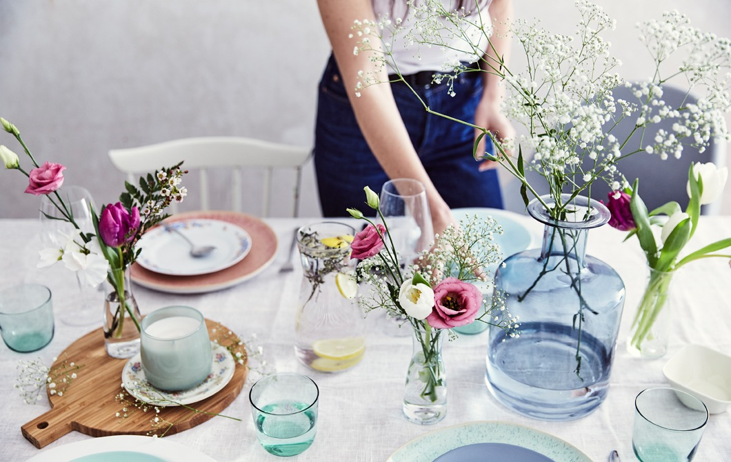 A table set with pastel tableware and fresh flowers in glass vases of different shapes and sizes, with a wooden board and cotton tablecloth.