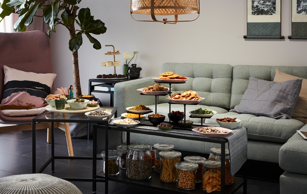 Living room side with corner sofa and armchair, fronted by a set of nest tables laden with snacks, both stored and served.