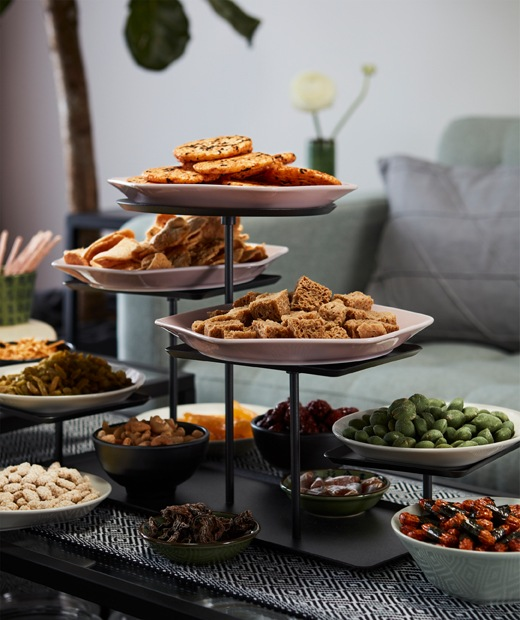 Multi-level display stand and many small bowls filled with a variety of snacks, standing on a coffee table next to a sofa.