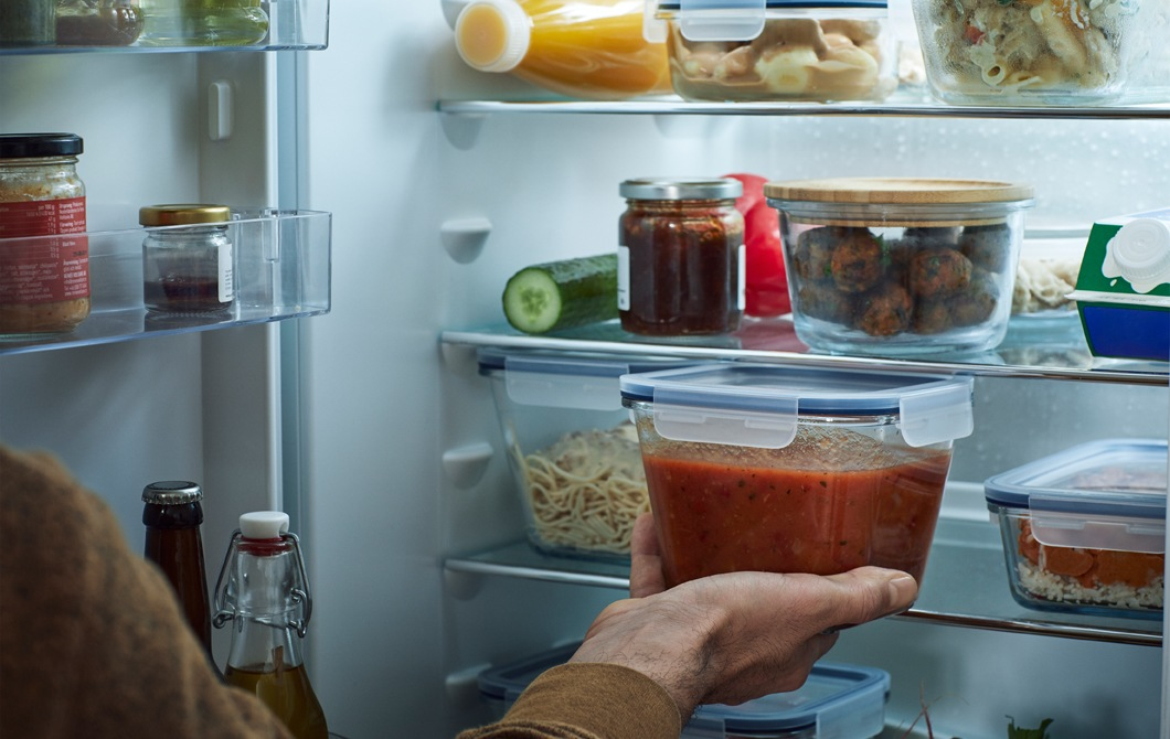 An open fridge with its shelves full of transparent containers of food.