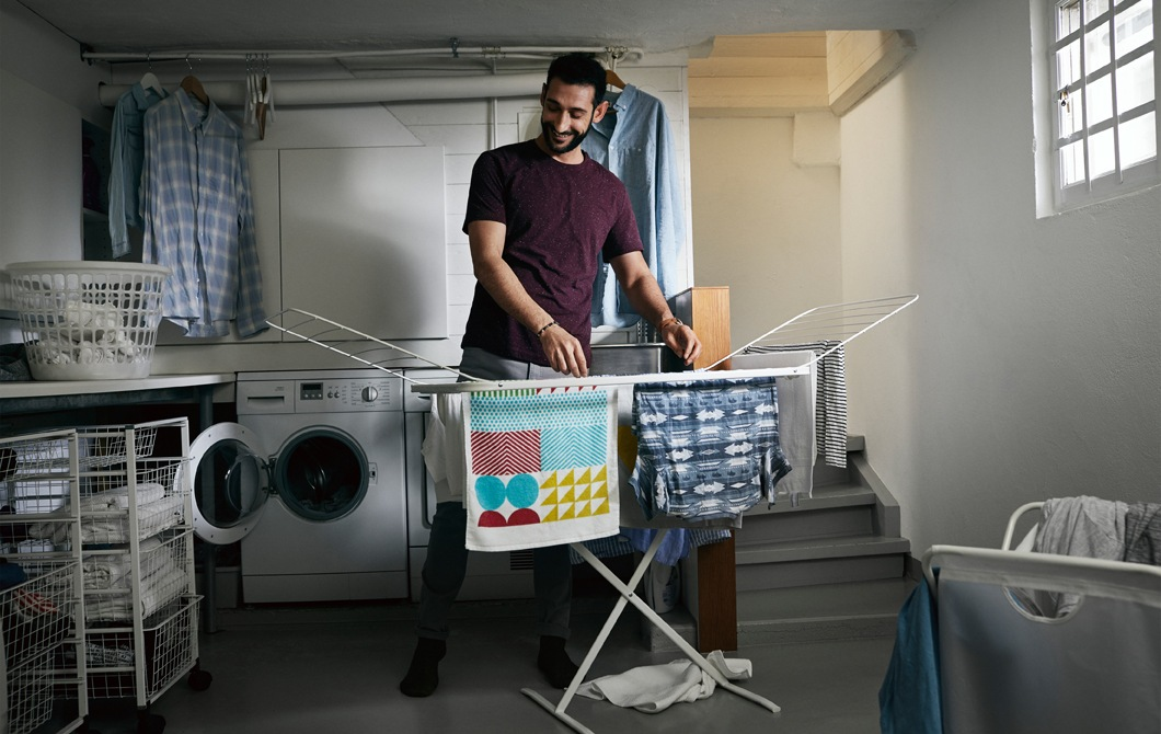 A person hanging clothes on an air dryer in a laundry room.