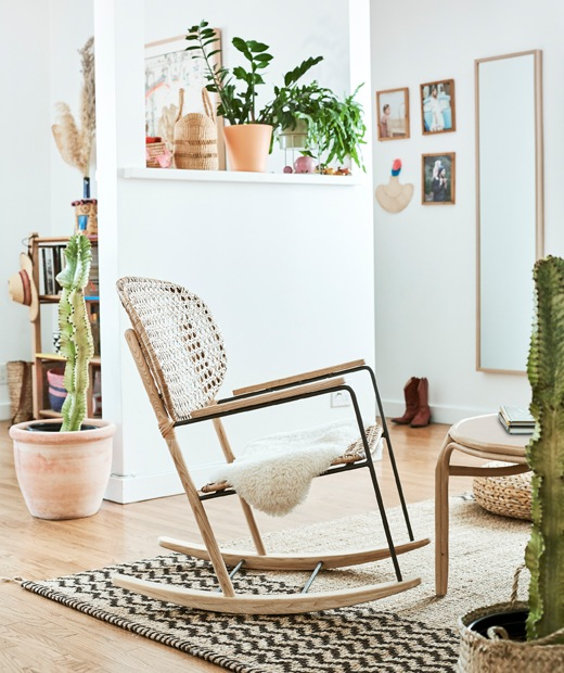 A living room with leather A rattan rocking chair on a hessian rug in a white room, with plants on a shelf and cacti in large pots on the wooden floor., rattan rocking chair, hessian rug, wooden floors, and two yellow stools along a countertop.