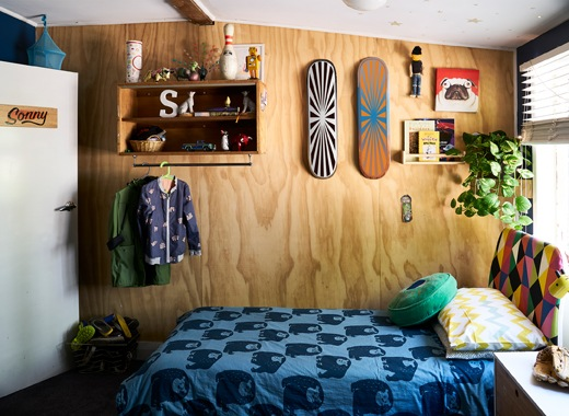 A child's bedroom with shelves and skateboards on a wooden wall, and blue patterned bedding.
