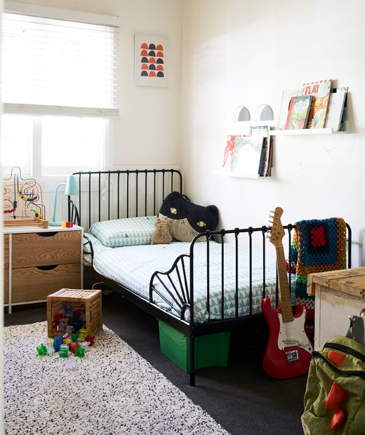 A child's bedroom with white walls, a black bed frame and books on picture ledges.