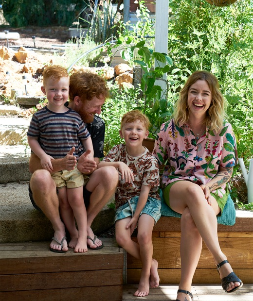 Nici, Ben and their two children sitting on decking in the garden.