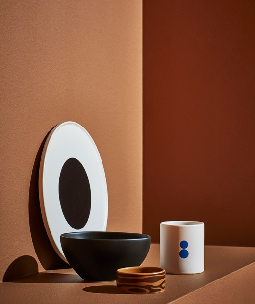 A white plate with black centre, large black bowl, small brown bowl and white mug on an orange step.