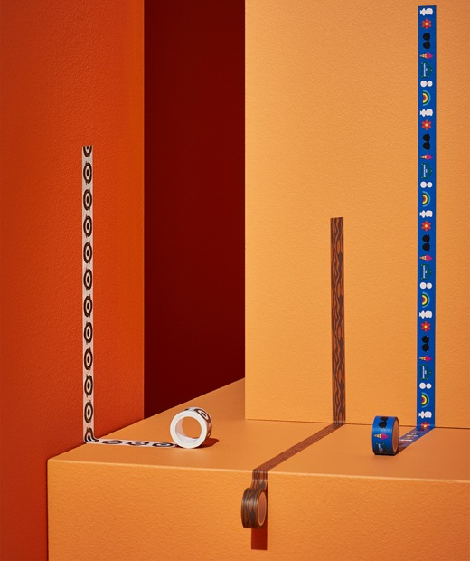 Three rolls of patterned washi tape rolled out on orange and red walls and steps.
