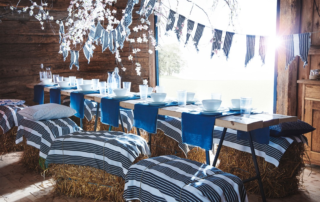 A long table in a wooden barn with blue and white tableware, and striped fabric used as bunting and tied on hay bales used as seats.
