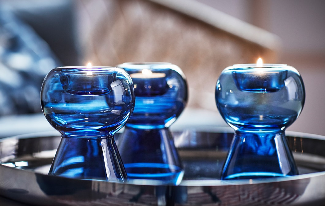 Three tealight holders made of blue glass on a silver tray.