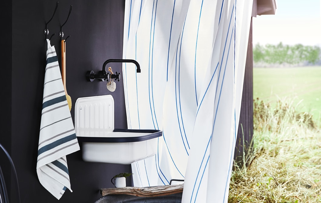 A towel, hooks, a sink and a tap on a black wall, with a field behind a striped shower curtain.