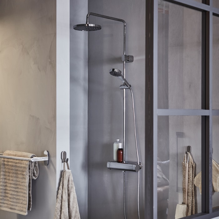 A grey shower cubicle with overhead shower and handheld shower, with beige towels hung on hooks.
