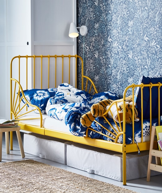 A child's bed with yellow frame and blue floral bedding, with boxes underneath and a wall lamp above.