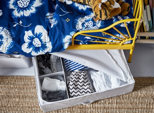Clothes in an open storage box under a child's bed with yellow frame and blue floral bedding.