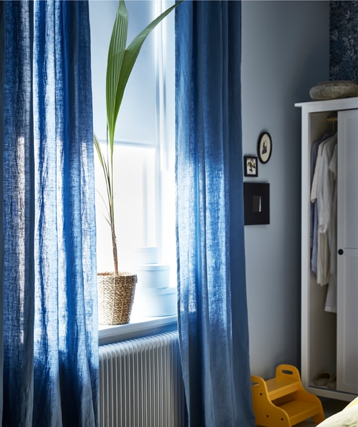 A window with white roller blinds, blue sheer curtains and a pot plant, next to an open wardrobe.