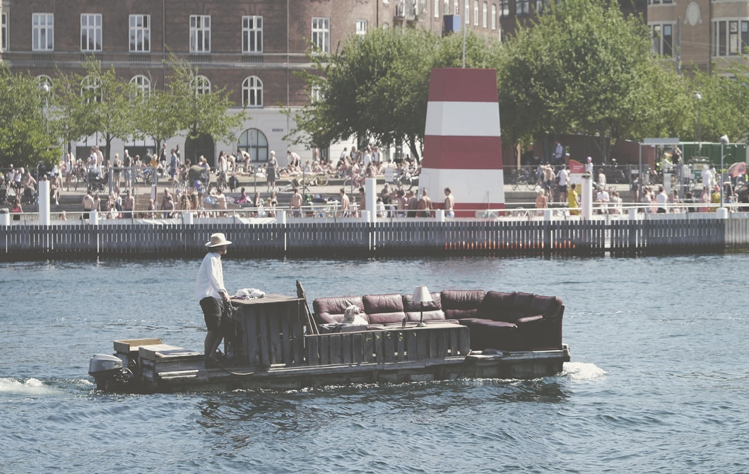 A man steers a large sofa on a raft along a river, with crowds of people, buildings and trees on the bank.