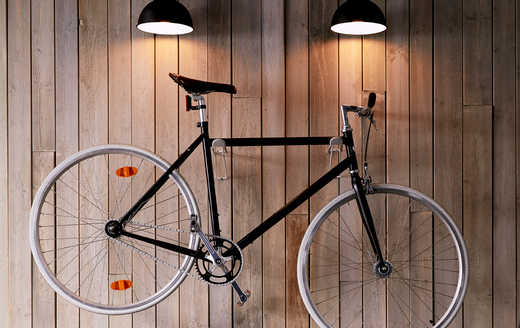 Sleek city bike hung in display fashion on a living room wall above floor cabinets and lit from above with wall lamps.