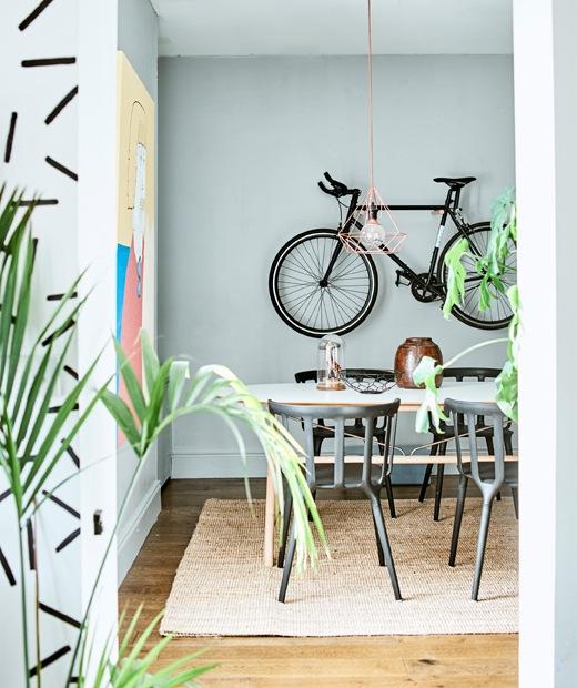 Dua anak duduk di dekat meja kayu terang dengan sarapan dan mainan, di depan dinding bata merah.
