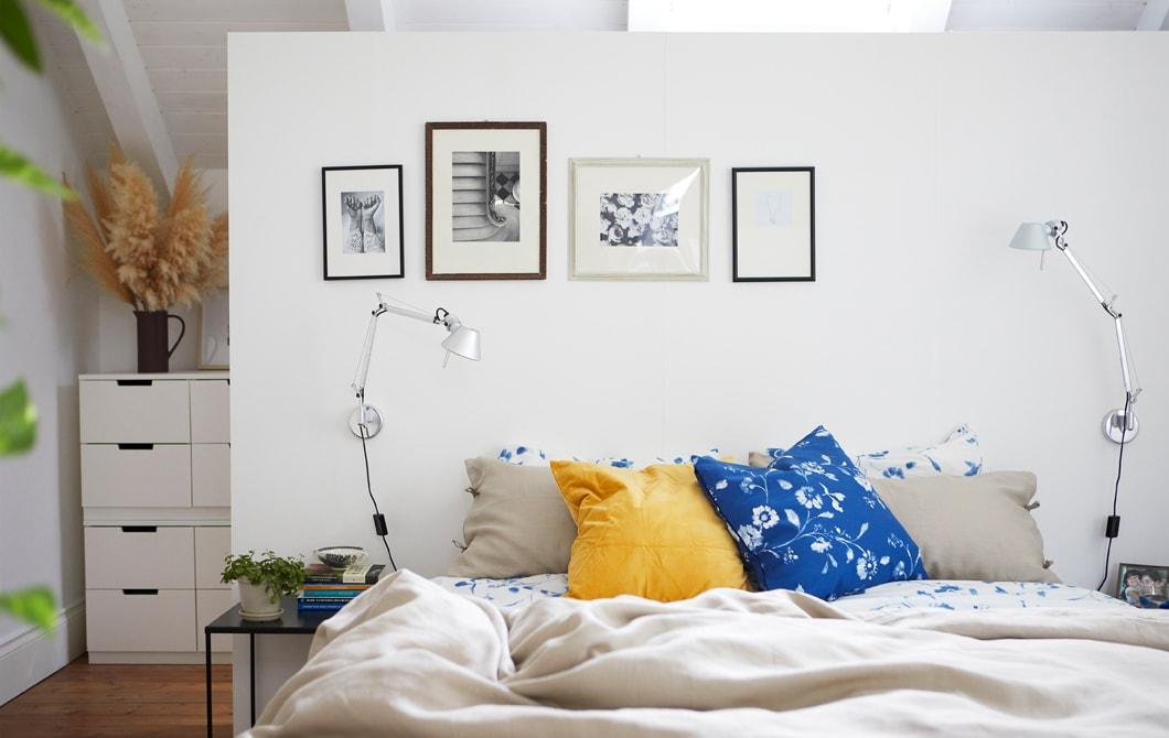 Sebuah ruang tidur berwarna putih dengan seprai netral dan motif bunga, dengan foto hitam-putih di dinding.