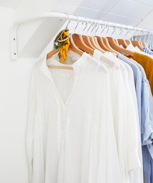 Pakaian di area penyimpanan yang sempit dengan laci, rak dan rel.