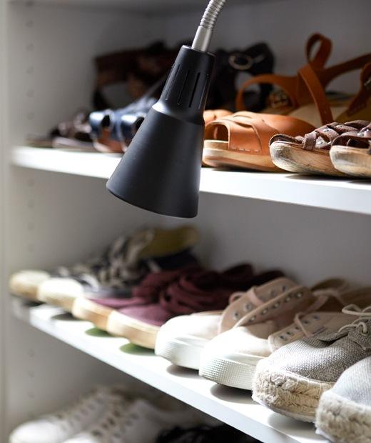 Sebuah topi rotan tergantung di sebuah pengait di sebuah rel di dinding putih. Sepatu berjejer di rak dengan lampu kerja berwarna hitam.