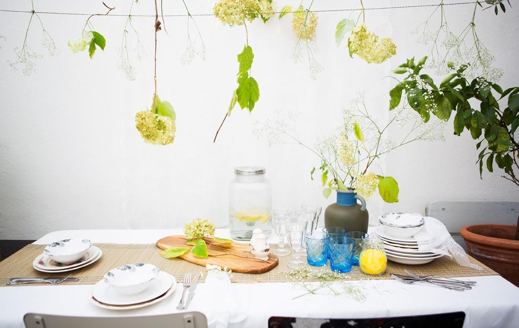 Tatanan meja makan dengan pecah belah bermotif, gelas, dan vas bunga, dengan rangkaian bunga yang bergantungan dari atas.