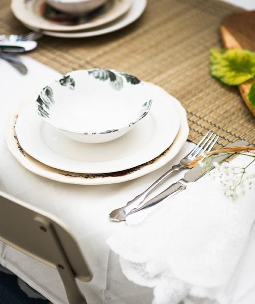 Beberapa gelas kaca berwarna biru dan gelas wine kaca bening di atas taplak meja panjang.