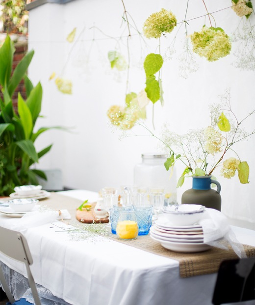 Tumpukan pecah belah dan set alat makan di taplak meja panjang dari mendong dan taplak meja putih.