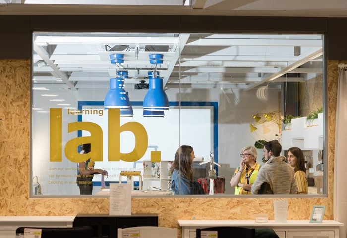 IKEA co-workers talk to customers behind a window with 'learning lab' written on the glass.