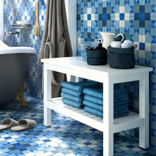 Sebuah bangku warna putih dengan handuk di rak bawah dan aksesoris di bagian atasnya, dengan dinding dan lantai ubin warna biru.