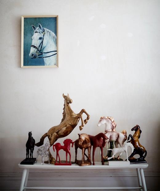 Koleksi ornamen kuda di atas bangku putih dan lukisan kuda di dinding atas.