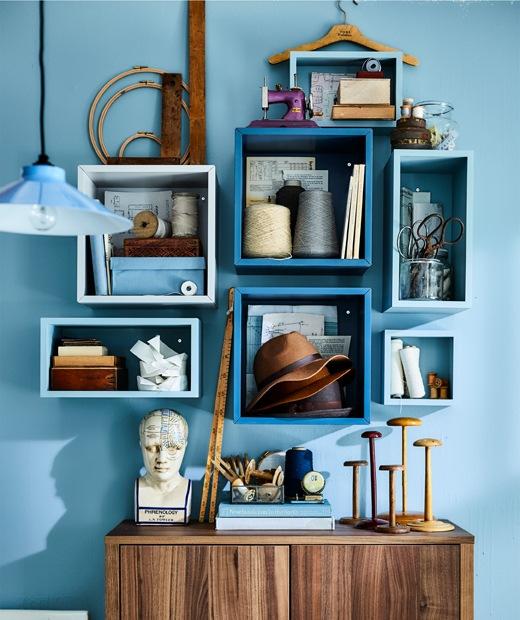 Perlengkapan menjahit dan buku tersimpan di rak kubus  yang ada di dinding warna biru.