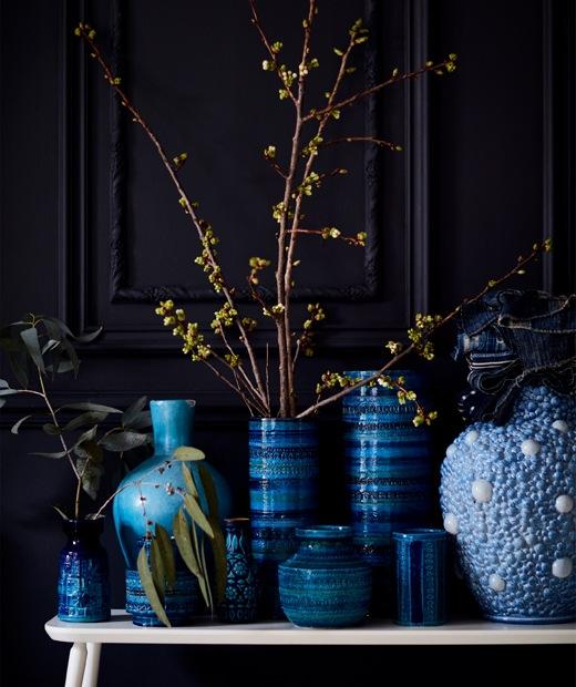Koleksi vas biru di atas bangku putih.