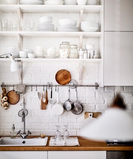 Barang pecah belah warna putih disimpan di rak terbuka di atas wastafel dapur dan meja dapur berbahan kayu.
