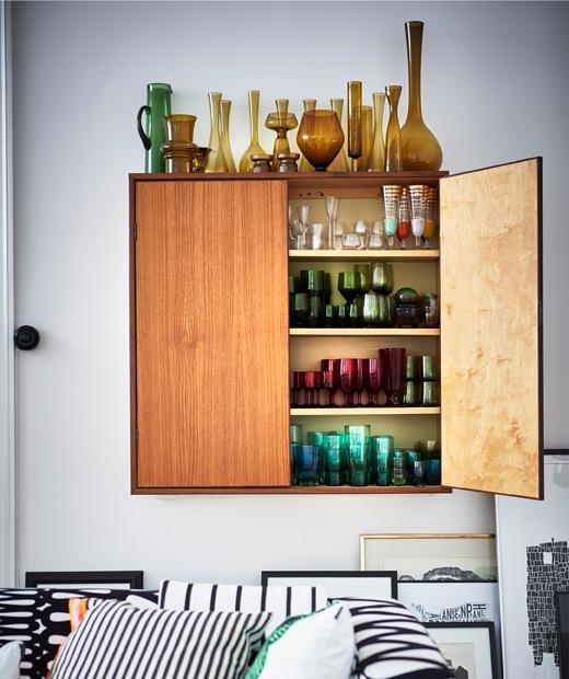 Vas kaca disimpan di dalam dan di atas sebuah kabinet dinding, dikelompokkan berdasarkan warna.