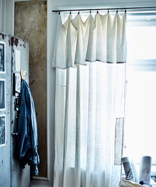 A sheer curtain hangs across a window next to a metal cabinet.