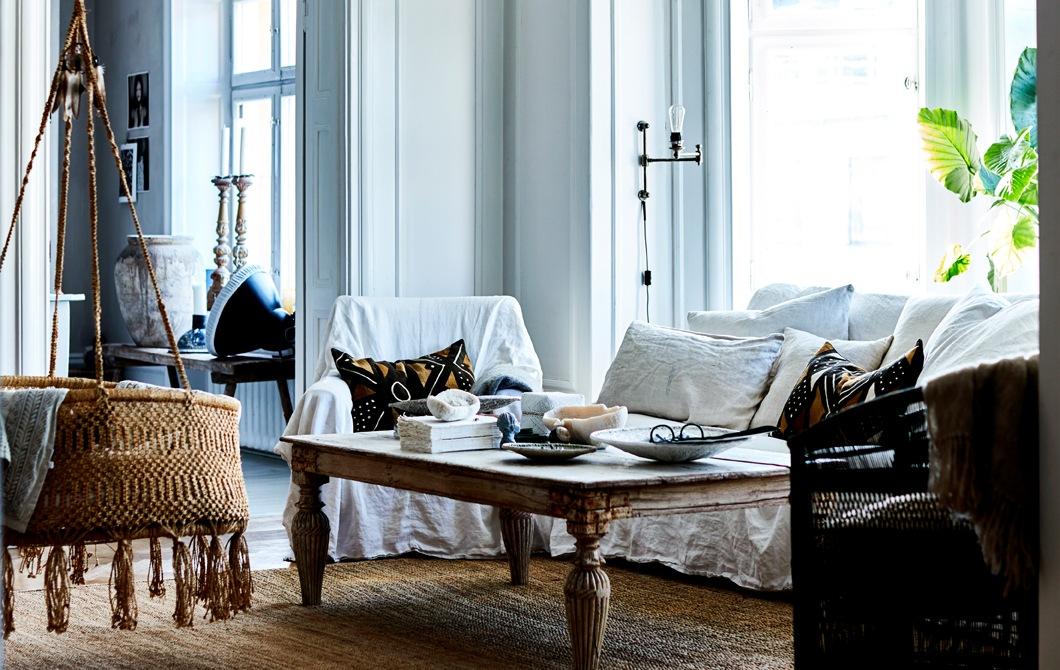 Sebuah ruang keluarga dengan sofa putih, meja bertema rustic dan kursi gantung rotan.