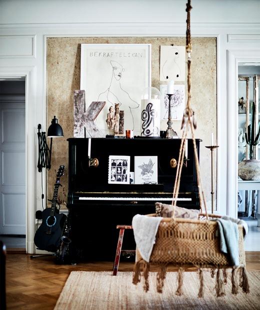 Piano hitam dan kursi gantung rotan di sebuah ruangan dengan lantai kayu.