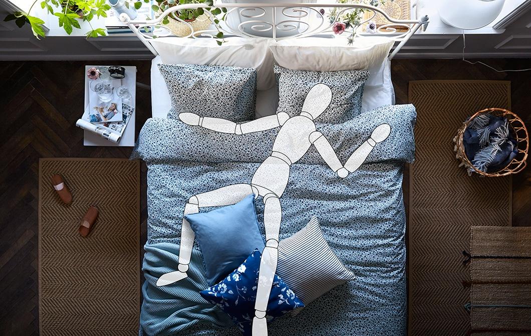 Interior kamar tidur dengan sebuah kasur berukuran besar. Boneka ilustrasi dengan posisi tangan dan kaki menyebar terbaring di atasnya.