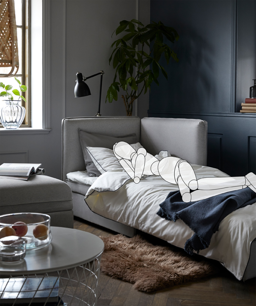 A sofa made for sleeping in a living room. The superimposed, sketched person lies on the side, a book on the side table.