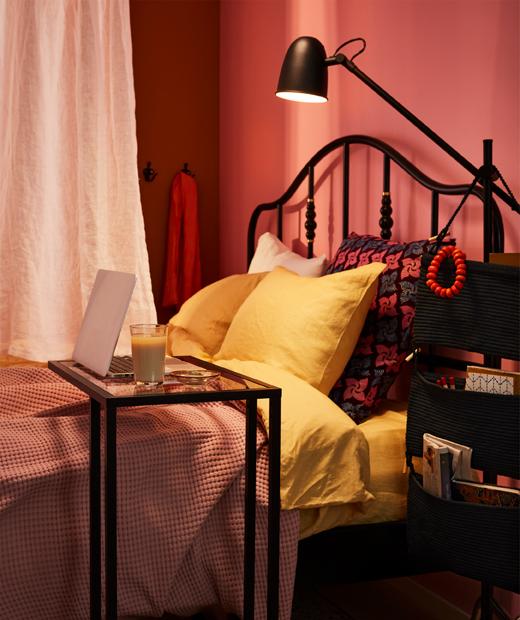 Tempat tidur lebar dan penuh warna dengan banyak bantal dan sebuah papan catur di atasnya. Seprai diletakkan di dalam kotak di bawahnya.