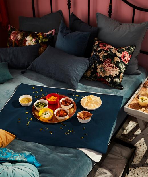 Tempat tidur lebar dan penuh warna dengan banyak bantal dan sebuah papan catur di atasnya. Meja nampan dengan minuman di atasnya berada di samping tempat tidur.