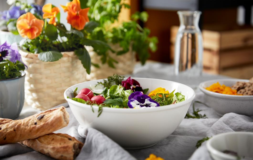 Sebuah tatanan meja untuk sarapan dengan berbagai jenis roti, vas bunga, dan semangkuk sayuran hijau dengan hiasan warna-warni.