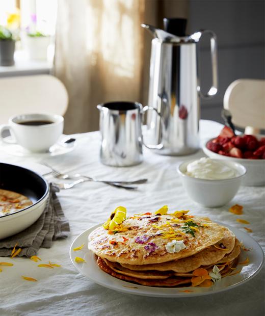 Meja dialasi taplak yang diatur untuk sarapan, dengan termos kopi, stroberi dengan krim dan sepiring kue panekuk yang dihiasi bunga.