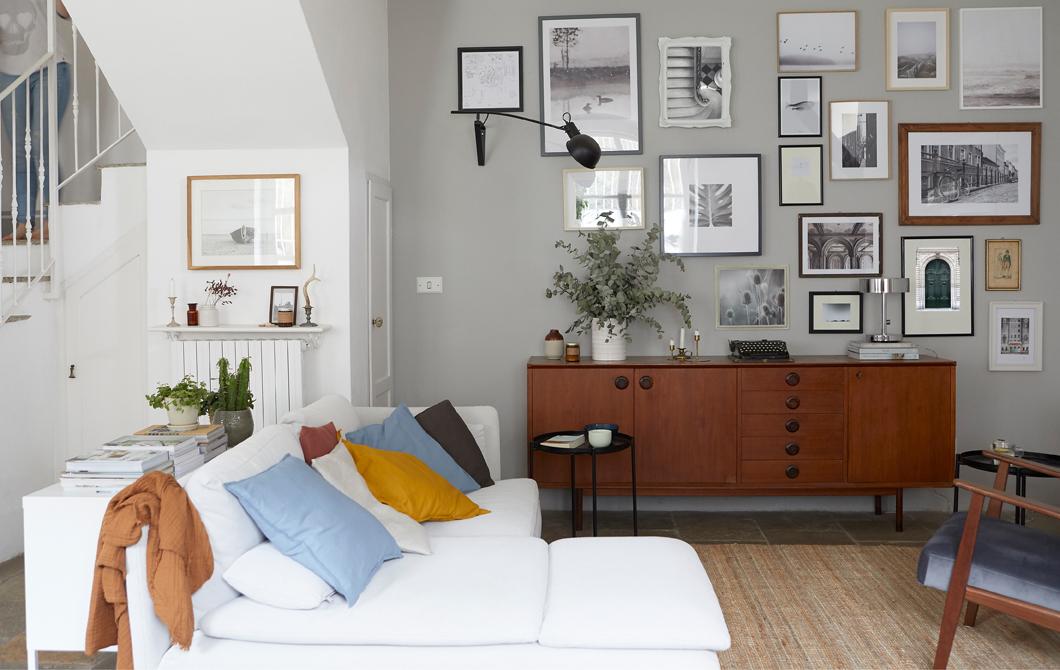 Ruang tamu dengan sofa sudut berwarna putih, papan samping kayu gelap dan galeri foto di dinding