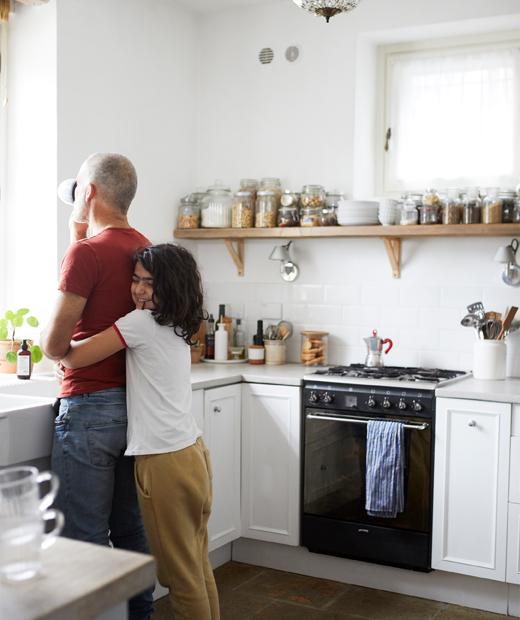 Kehidupan dengan perencanaan terbuka, area ruang makan dan dapur, dengan dinding berwarna putih, sofa putih dan dapur putih.