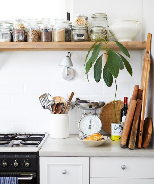 Gigi dan putrinya berpelukan di dapur serba putih dengan ubin putih dan stoples di atas rak kayu panjang.